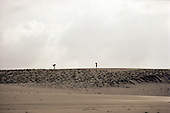 Ceara State, brazil. Two people carrying firewood on their heads silhouetted at the top of a sand dune.