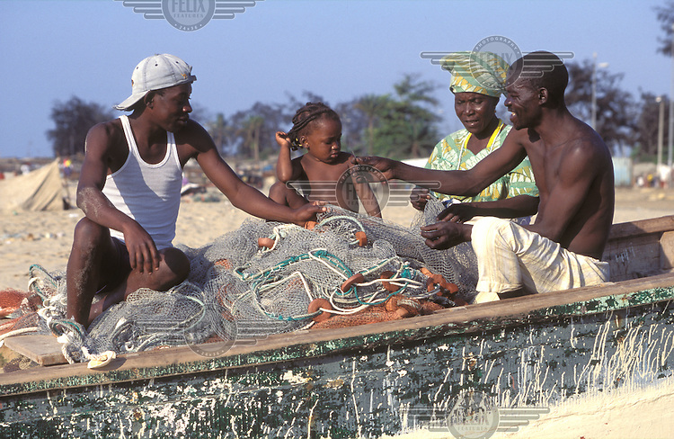 © Giacomo Pirozzi / Panos Pictures..ANGOLA..A family sorting out their fishing nets.