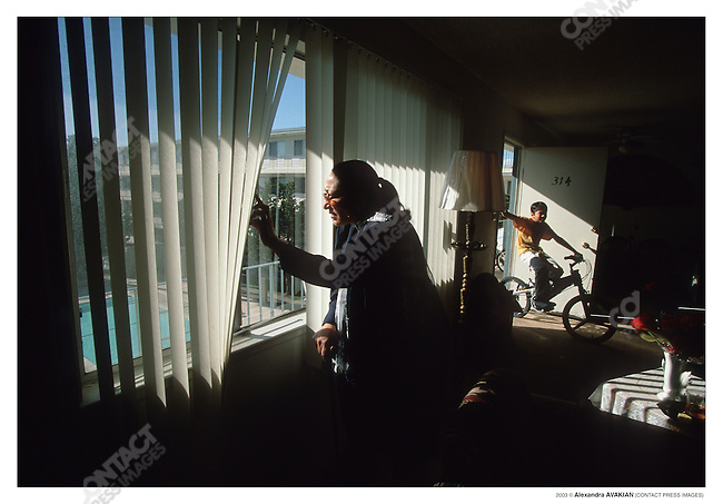 Asia Miskeenyar, 40, from Herat, Afghanistan. Looks out the window of her lower middle class apartment complex. Fremont, California, April 2002