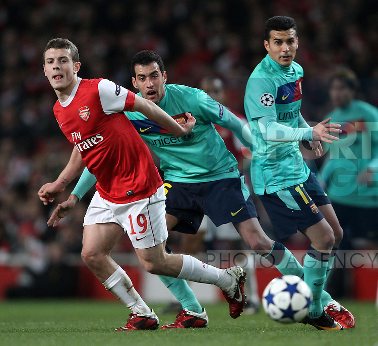 Arsenals Jack Wilshere tussles with Barcelonas Sergio Busquets and Pedro