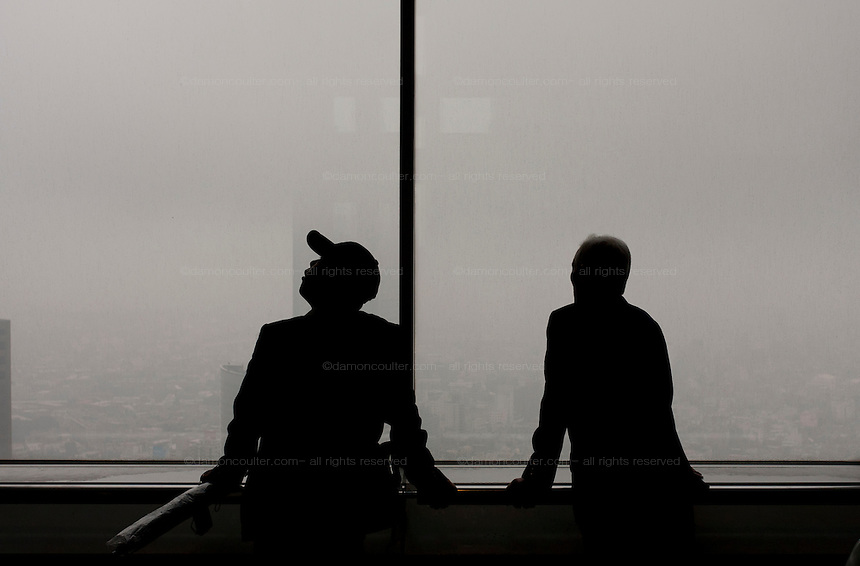 Tourists take in the view of a rainy Tokyo from the 45th floor observation deck of the Tokyo Metropolitan Government Tower in Shinjuku, Tokyo, Japan. Friday November 11th 2011