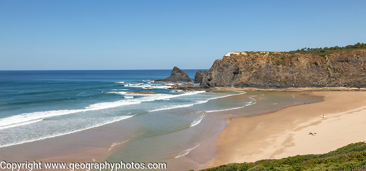 Coastline view of headlands and bay with wide sandy beach, surfer and a few sunbathers, Praia de Odeceixe, Algarve, Portugal, Southern Europe