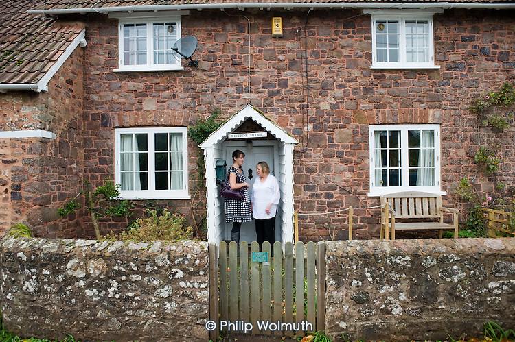 An outreach worker from housing support charity Wessex Reinvestment Trust , with a sight-impaired client in the village of Wooton Courtenay, Somerset.