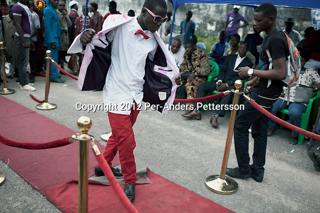 """KINSHASA, DEMOCRATIC REPUBLIC OF CONGO - FEBRUARY 10: A young Sapeur parades and shows his designer label clothes, including Versace, while paying their respect to Stervos Nyarcos, the founder of the kitendi religion, which means clothing in local language Lingala. Nyarcos was known as the leader of the Sape movement, at Gombe cemetery on February 10, 2012 in Kinshasa, DRC. The word Sapeur comes from SAPE, a French acronym for Société des Ambianceurs et Persons Élégants or Society of Revellers and Elegant People and it also means, to dress with elegance and style"""". Most of the young Sapeurs are unemployed, poor and live in harsh conditions in Kinshasa,  a city of about 10 million people. For many of them being a Sapeur means they can escape their daily struggles and dress like fashionable Europeans. Many hustle to build up their expensive collections. Most Sapeurs could never afford to visit Paris, and usually relatives send or bring clothes back to Kinshasa. (Photo by Per-Anders Pettersson)"""