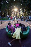 Children playing on merry-go-round at sunset, Dottie Harper Park, Burien, WA, USA.