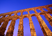 Abstract view of the ruins of a Roman Aquaduct (1st century AD) in contrast to a bright blue twilight sky. Segovia, Spain