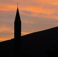 Tower of the Franciscan monastery of St Peter and Paul, the new catholic church built in 2000 to replace the original 1866 building which was destroyed in the 1990s Yugoslav Wars, silhouetted against the sky at sunset, in Mostar, Bosnia and Herzegovina. The town is named after the mostari or bridge keepers of the Stari Most or Old Bridge. Mostar developed in the 15th and 16th centuries as an Ottoman frontier town and is listed as a UNESCO World Heritage Site. Picture by Manuel Cohen
