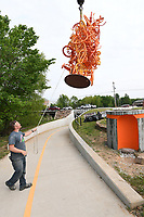 NWA Democrat-Gazette/J.T. WAMPLER Tylur French (CQ), a Memphis based artist, installs his bicycle sculpture Wednesday May 10, 2017 along the Razorback Greenway Trail near Walton Blvd. in Bentonville. The piece is one of a pair with the other installed near Lake Bentonville. Both sculptures are mounted to concrete bases that also house a working bicycle pump for passing riders.