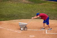 Lining a baseball diamond with lime.