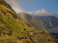 A rainbow pours over the Wai'anae Range (or Mountains), as seen from Ka'ena Point, O'ahu.