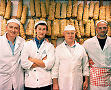 Italy, Orvieto, Umbria, smiling butcher family standing in front of packed meat for curing