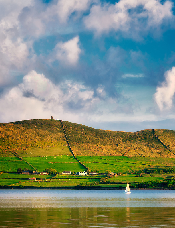 Hillside next to Dingle Bay at sunset with sailboat. County Kerry, Ireland