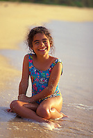 Little girl smiling and playing on the beach at the north shore
