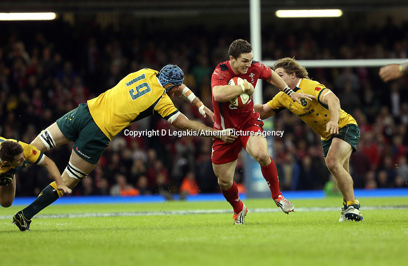 Pictured: George North of Wales (C) is tackled by James Hornwill (L) and Michael Hooper (R) of Australia. Saturday 08 November 2014<br /> Re: Dove Men Series rugby, Wales v Australia at the Millennium Stadium, Cardiff, south Wales, UK.