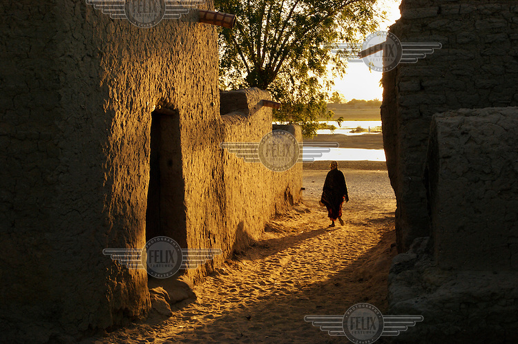 A person walks down a street in the town of Gao, located on the Niger River. /Felix Features