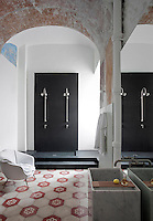 A centuries old barrel ceiling combines with a 20th century floor of concrete tiles in this bathroom furnished with a double shower of grey resin and a wash basin of veined marble