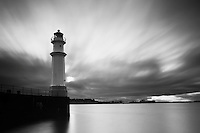 Lighthouse at the Newhaven Harbour, Edinburgh, Scotland.  .Newhaven is a district of the city of Edinburgh, at the north of the city, between Leith and Granton. The lighthouse and pier are a favorite spot with local fishermen.  .Long exposure.