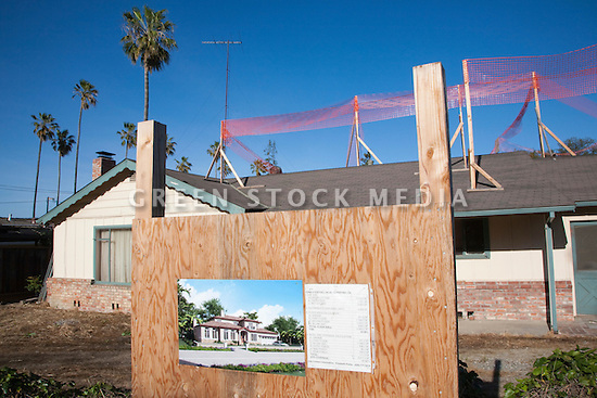 A signboard showing details of a new single family house construction project with the old house in the background, ready for development. A structure of orange plastic construction fence material signals the preparation for a major construction project. This one-story house on a 10,000 square foot lot is set to become a 4,060 square foot two story single family home with an in-law unit. Cupertino, California, USA