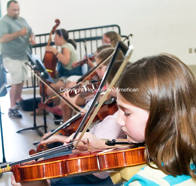 WOODBURY, CT- 26 JUNE 2007- 062607JT02-<br /> Felicity Petruzzi, 9, practices her violin as Walter Culup, background, instructs others during a summer strings program at Nonnewaug High School on Tuesday. Culup is the director of the new program, which consists of three hours of group instruction two days a week, and is also music coordinator for the district and band director at Nonnewaug.<br /> Josalee Thrift Republican-American