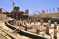 Foundation construction for a tall building tower block with diaphragm wall, pile caps under construction and concrete pumping equipment.  Dubai. United Arab Emirates.