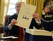 United States President Donald J. Trump displays his signature after signing the $1.5 trillion tax cut bill, stacked on his desk, in the Oval Office of the White House, December 22, 2017, in Washington, DC, prior to his departure to Mar-a-Lago, Florida for the holidays.    <br /> Credit: Mike Theiler / Pool via CNP