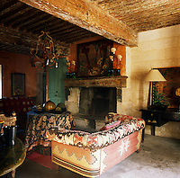 A rustic sitting room with a heavy beamed ceiling and a stone fireplace. The walls are painted a warm orange and the room is furnished with a kilim-covered sofa