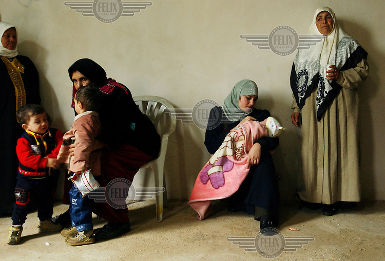 Mothers and grandmothers wait with their children for medical treatment at a mobile clinic set up by Israeli doctors in the West Bank village of Brukin.