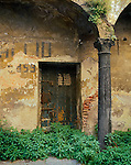 Lucca, Tuscany, Italy<br /> Iron door and pillar in an old courtyard