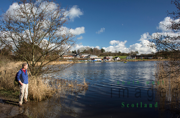 Early spring sunshine walker looking across Castle Loch to Annandale Sailing Club, Lochmaben, Scotland. UK