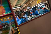 Salvadorean hairdressers cut customers' hair in a vintage barber shop in San Salvador, El Salvador, 14 May 2011.