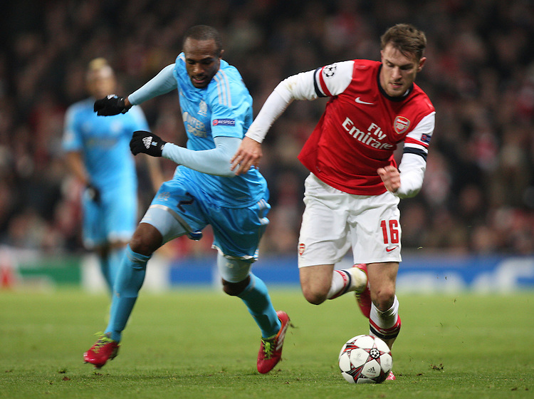 Arsenal's Aaron Ramsey despite the attentions of  Marseille's Kassim Abdallah<br /> Photo by Kieran Galvin/CameraSport<br /> <br /> Football - UEFA Champions League Group F - Arsenal v Marseille - Tuesday 26th November 2013 - The Emirates Stadium - London<br /> <br /> &copy; CameraSport - 43 Linden Ave. Countesthorpe. Leicester. England. LE8 5PG - Tel: +44 (0) 116 277 4147 - admin@camerasport.com - www.camerasport.com