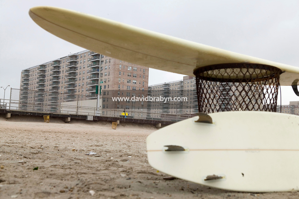 A surfboard rests on a trash can at Far Rockaway beach in New York, United States, 17 September 2005. Photo Credit: David Brabyn.