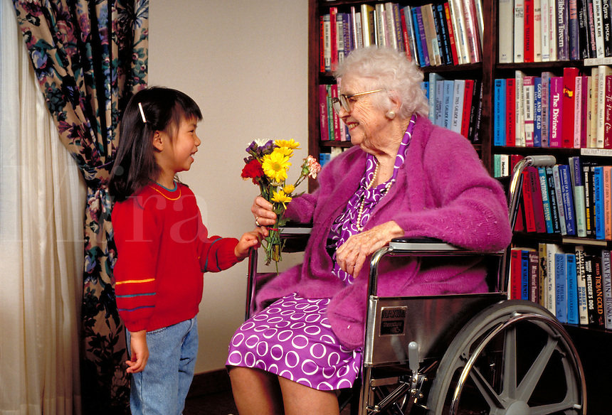 2ND GRADE CHINESE AMERICAN GIRL GIVES SENIOR LADY FLOWERS IN RETIREMENT HOME. SENIOR AND YOUNG GIRL. OAKLAND CALIFORNIA.