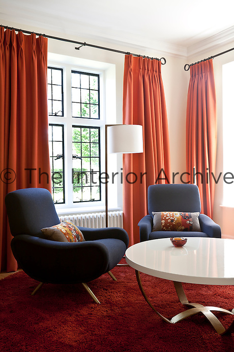 A pair of grey retro armchairs in the living room with orange curtains and shag-pile rug