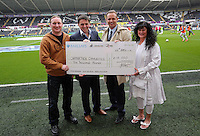 Sunday, 26 April 2014<br /> Pictured: Leigh Dineen and Lee Trundle present Carmarthen Gymnastics with a Swans Aid cheque.<br /> Re: Barclay's Premier League, Swansea City FC v Aston Villa at the Liberty Stadium, south Wales.