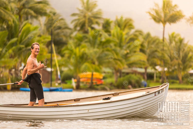 "Older, fit surfer smiles and flashes a ""shaka"" as he rides his classic boat out to surf Hanalei Bay, Kaua'i."