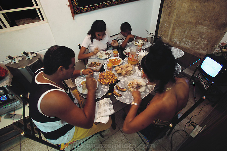 Ramon Costa and Sandra Raymond and their teenaged daughter, Lisandra, and 6-year-old son Favio eat dinner in the narrow 2-story makeshift apartment behind Ramon's father's house in the Marianao district of Havana. They are eating a dinner of rice and beans, French-fried malanga, salad, fresh orange juice, and bananas. From coverage of revisit to Material World Project family in Cuba, 2001.