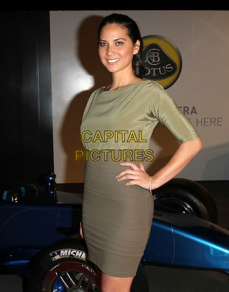 OLIVIA MUNN .U.S. Launch Event for New Lotus Carst held at A Private Residence, Los Angeles, CA, USA, .12th November 2010..half length  green silk satin khaki dress hand on hip .CAP/ADM/KB.©Kevan Brooks/AdMedia/Capital Pictures.