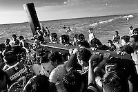 Catholic followers carry the wooden cross in the sea during the annual Holy Week ritual (Lavado de la cruz) in Santa Elena, Ecuador, 3 April 2012.