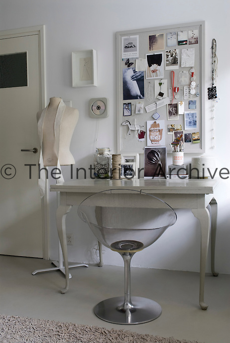 A notice board designed to inspire hangs above a contemporary work table in the bedroom