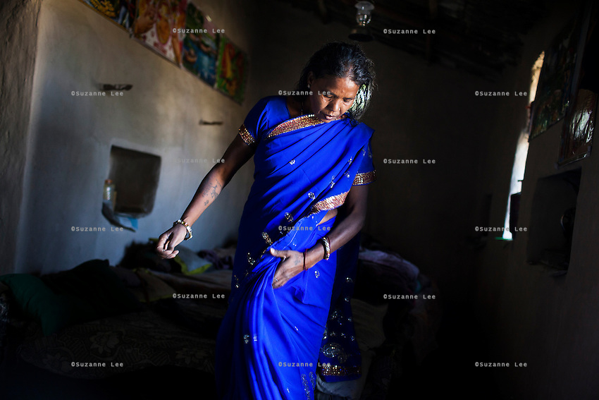 Shanti Adivasi, 52, gets dressed in her home, where she lives with her 3 generation family of 14, in Manikpur, Chitrakoot, Uttar Pradesh, India on 6th December 2012.  Shanti used to be a wood gatherer, working with her parents since she was 3, and later carrying up to 100 kg of wood walking 12km from the dry jungle hills to her home to repack the wood which sold for 3 rupees per kg. After learning to read and write in an 8 month welfare course, at age 32, she became a reporter, joining Khabar Lahariya newspaper since its establishment in 2002, and making about 9000 rupees per month, supporting her family of 14 as the sole breadwinner. Photo by Suzanne Lee for Marie Claire France.