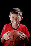 Boy with basketball on black background