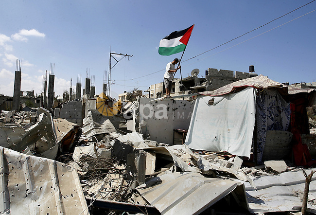 "A Palestinian man holds a national flag to hang on the rubble of a destroyed house in Khan Yunis in the southern Gaza Strip on September 11, 2014. Israel's deputy foreign minister,Tzahi Hanegbi , warned that Hamas was likely to resume ""violence"" if it feels it has made no political gains from upcoming talks in Cairo. Photo by Abed Rahim Khatib"