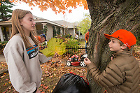 NWA Democrat-Gazette/BEN GOFF @NWABENGOFF<br /> Medeline Suggs of Lewisville, Texas, shows a large leaf she found to Nash Courtney, 11, of Rogers while helping rake up leaves Saturday, Nov. 3, 2018, at Nicole's House in Rogers. The two families were volunteering to do fall yardwork at the transitional living facility for women recovering from drug and alcohol addiction.
