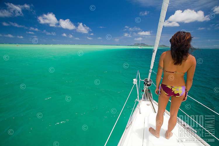 Young girl in bikini on the bow of a sailboat in Kaneohe Bay, Oahu, Hawaii