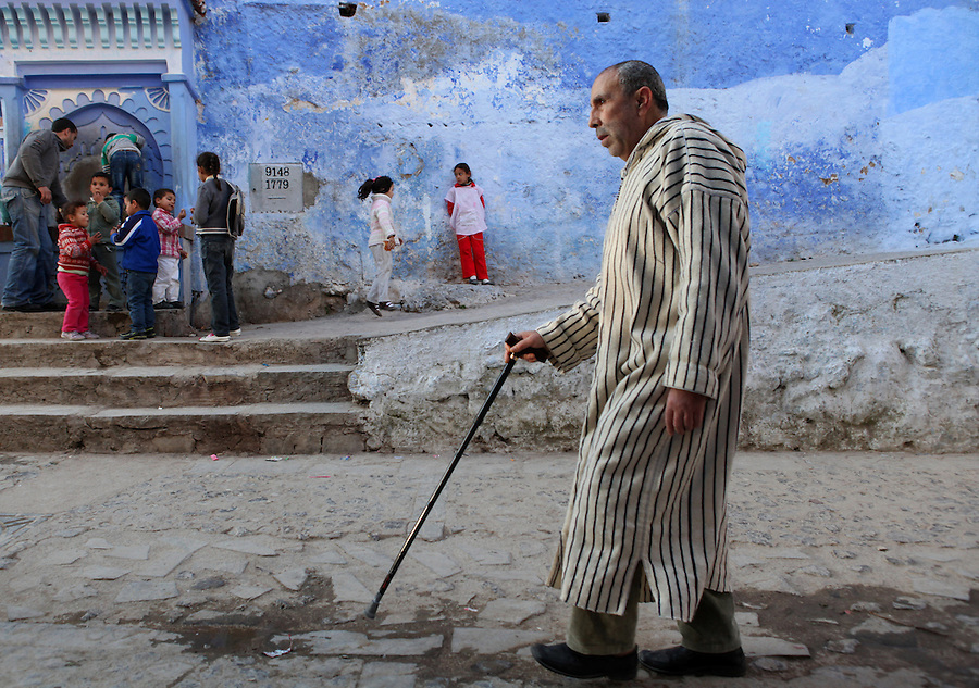 """A blind man walks past one of the public drinking fountains where children are gathered in Chefchaouen, Morocco, whose """"medina"""" (old city) is famous for its striking blue walls."""