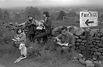 Appleby in Westmorland traditional annual gypsy Horse Fair Cumbria. Traveller family eating fish and chips out of newspaper. Sign to Fair Hill. 1981