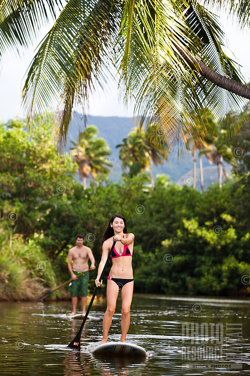 A couple standup paddling on the Anahulu River on the North Shore of Oahu