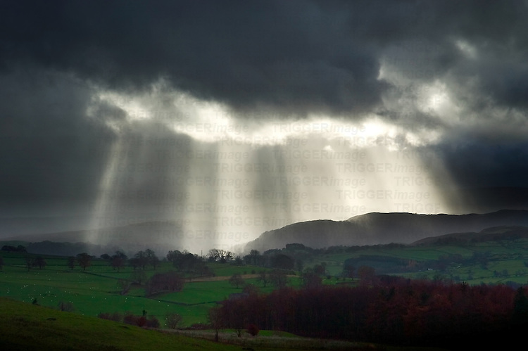 Rays of sunlight shining through dark clouds over an English landscape