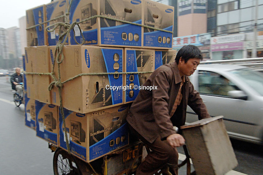 "Worker carrying loads of Samsung computer monitors with a bike in Chengdu, China. Chengdu is one of western China's largest cities and the Government is encouraging investment with it's ""Go West"" campaign.."